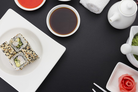 speciality: Sushi roll with fresh ingredients with ginger wasabi over black background