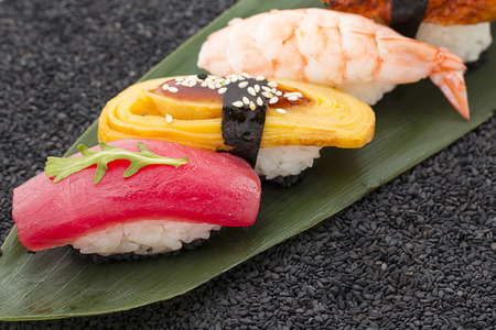 speciality: Sushi nigiri set on a bamboo list and black sesame background
