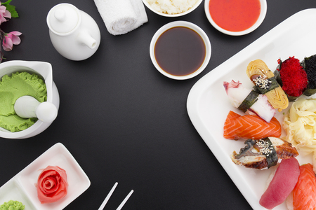 Sushi nigiri on a white plate with ginger wasabi and sauces over black background
