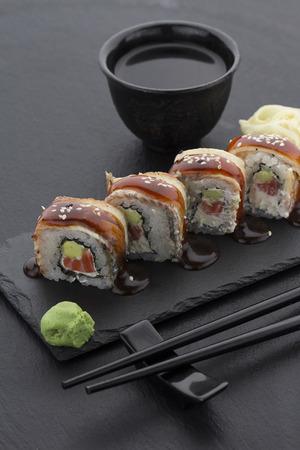 生姜ワサビ醤油と箸と皿の上の黒い背景転がしてうなぎ寿司