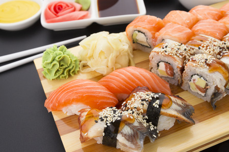 Japanese cuisine. Sushi set on a wooden plate over black background.