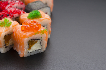 speciality: Japanese cuisine. Set of sushi mix roll with different fresh ingredients over black background