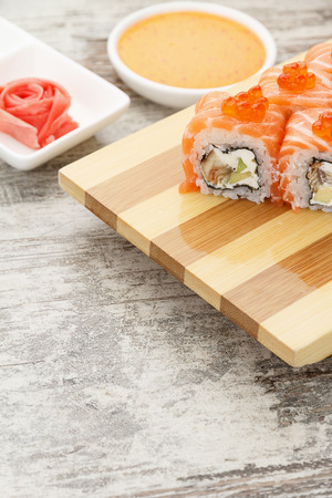 speciality: Japanese cuisine. Sushi roll with wasabi and ginger on a rustic table.