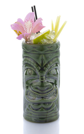 tropical cocktail: Tropical cocktail served in a tiki style glass and garnished with fruits isolated on white background