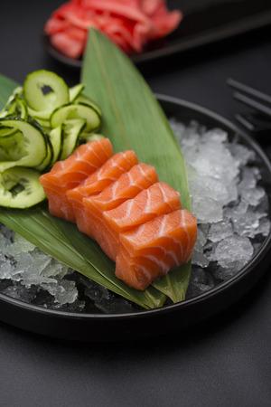 susi: Japanese cuisine. Salmon sashimi on ice over black background.