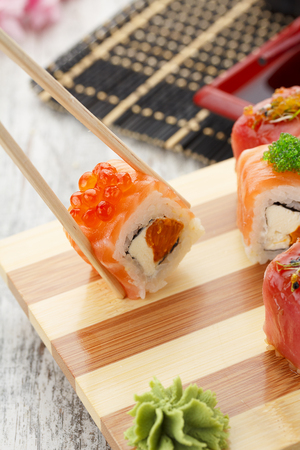 susi: Japanese cuisine. Sushi set and one peace of roll in chopsticks.