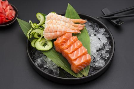 japanese cuisine: Japanese cuisine. Salmon sashimi on ice over black background.