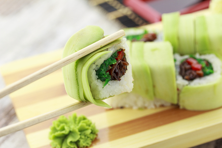 Sushi rolls with avocado on a wooden plate ( gete ).