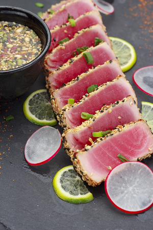 ahi: Tuna fillet with sesame decorated with limon and vegetables on a stone plate.