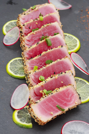 limon: Tuna fillet with sesame decorated with limon and vegetables on a stone plate.