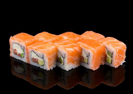 susi: Japanese cuisine. Salmon sushi roll over black background. Stock Photo