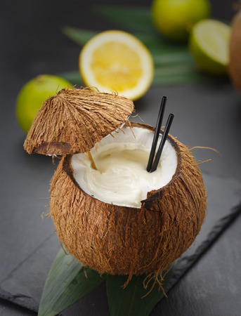 tropical drink: Coconut cocktail on a black table with lemon and kiwi.