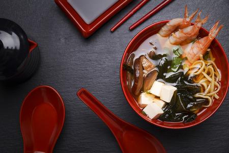 sopa de miso japonesa en un recipiente de color rojo sobre la mesa.