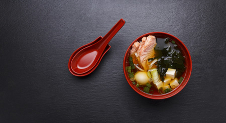 hashi: Japanese miso soup in a red bowl on the table.