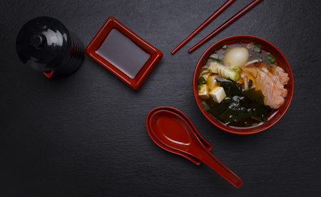 dashi: Japanese miso soup in a red bowl on the table.