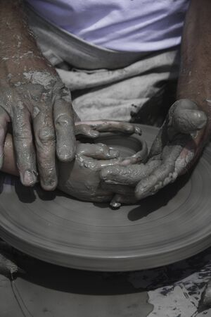 guiding: A mens hands guiding a child hands to help him to work with raw clay Stock Photo