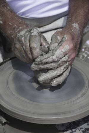 potters wheel: potters hands with the product on a potters wheel