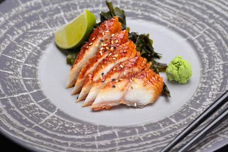 Japanese cuisine. Sushi. Eel  sashimi on a round plate Stock Photo