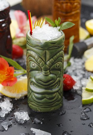 Tropical cocktails served in a tiki style glass and garnished with fruits and ice