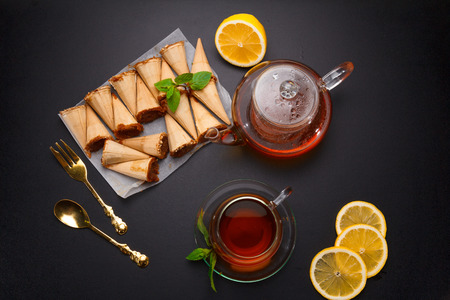 Homemade honey wafers rolled into a cone, filled with condensed milk, a cup of tea and lemon on a black table Stock Photo