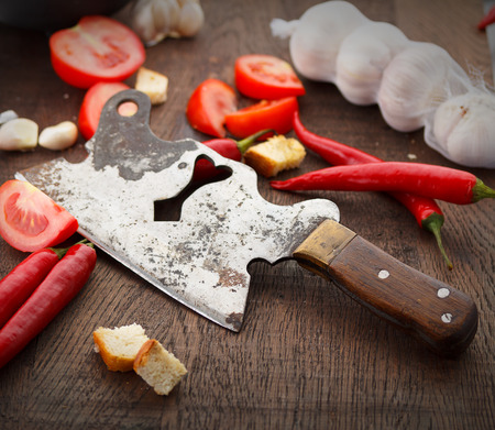 Fresj tomatoes, garlik and old knife on a wooden table