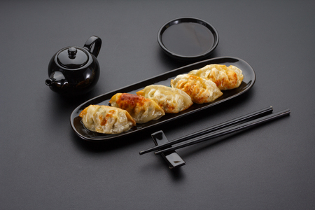 A plate of Japanese gyoza over black background Stock Photo