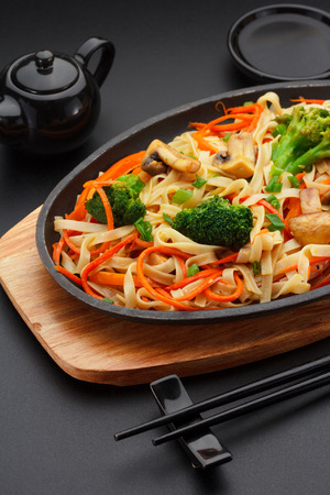 Asia food. Udon noodles with vegetables on a black table