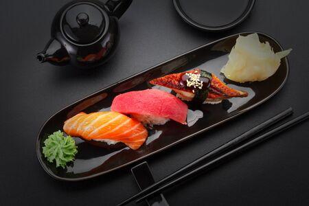 Atún, salmón y anguila nigiri sushi en la tabla negro