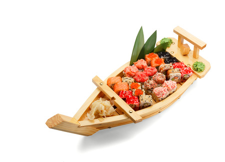 Japanese cuisine. Sushi set in a boat isolated on white bacground.