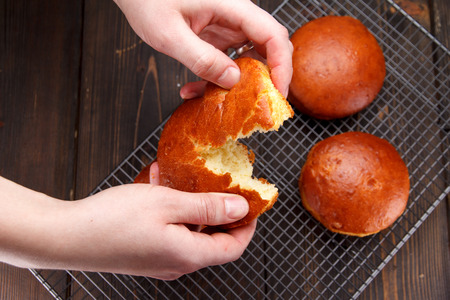 Tasty fresh newly-baked buns on a iron grid over wooden background Stock Photo
