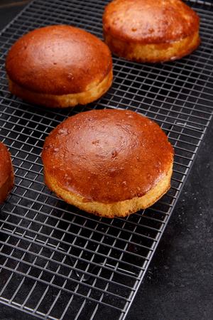 Tasty fresh newly-baked buns on a iron grid over stone background Stock Photo
