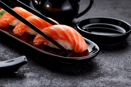 Japanese cuisine. Salmon sushi nigiri on a black plate with chopsticks. Stock Photo