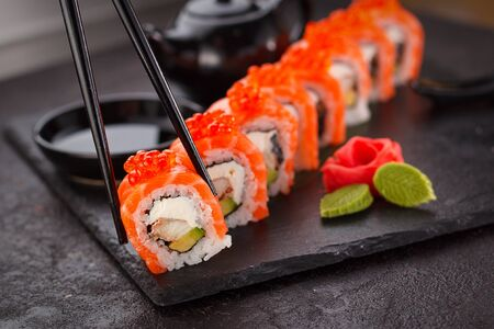 Japanese cuisine. Salmon sushi roll in chopsticks on a stone plate over concrete background. Banco de Imagens