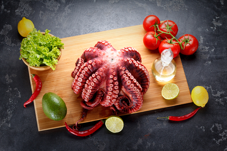 prepared: Freshly prepared octopus on a wooden board over dark stone background