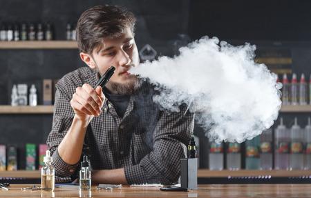 Vape bar (shop). Vaping man is smoking e-cigarette. A cloud of vapor.