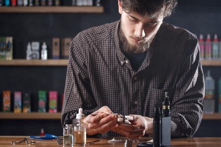 Vape. One man in a vape bar (shop) is repairing e-cigarette.