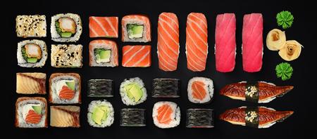 Japanese cuisine. Sushi with fresh ingredients over black background. Stock Photo