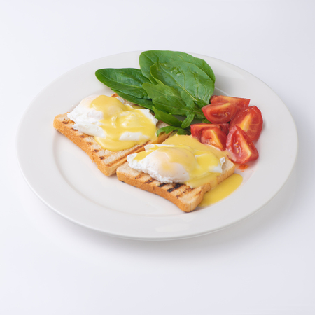 Plate of breakfast with fried eggs, toasts, tomato isolated on white backgound