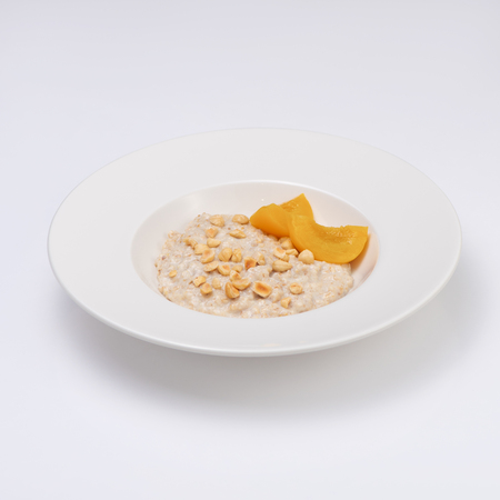 A plate of oatmeal porridge with nuts and peach. Hot and healthy breakfast every day, diet food.