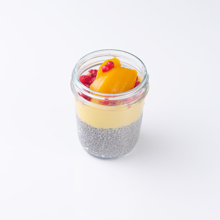 Sweet dessert in glass with fuits and seeds. Isolated on white background. Banco de Imagens