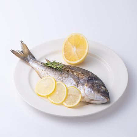 Dorada fish with lemon on a white plate.