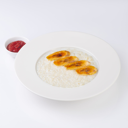 A plate of oatmeal porridge with fried banana. Hot and healthy breakfast every day, diet food. Banco de Imagens