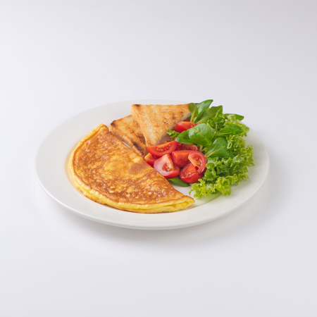 Plate of breakfast with omelette, toasts, tomato isolated on white.