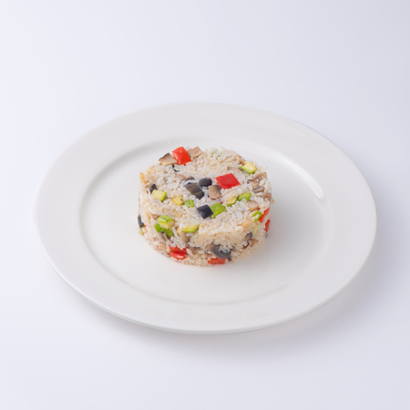 Rice with vegetables. Serving as in a restaurant. Isolated on white background.