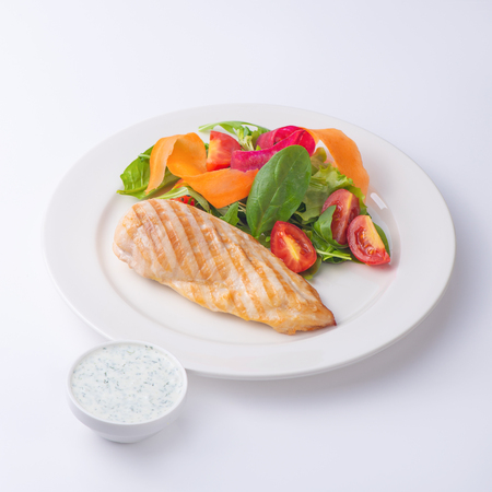 Chicken fillet steak with salad  and white sauce. Isolated on white background. Banco de Imagens