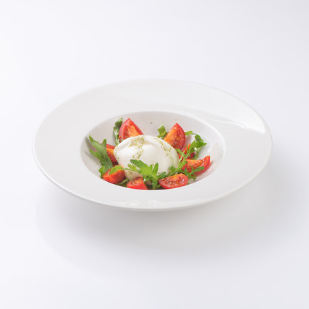 Salad with mozzarella on a white plate. Isolated on white background.