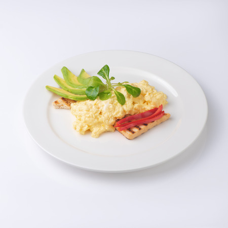 Scrambled eggs with toast and avocado. Isolated on white background.