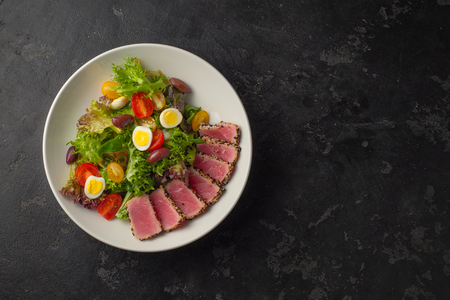 Sliced Steak of tuna in sesame and a salad of fresh vegetables and quail eggs.