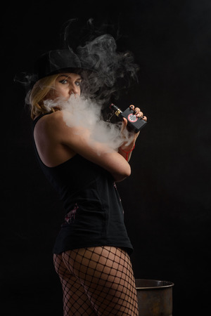 Young sexy woman is vaping. Studio shoot. E-cigarette. Smoke.