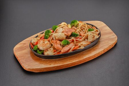 Thai dish. Udon noodles with vegetables and salmon.